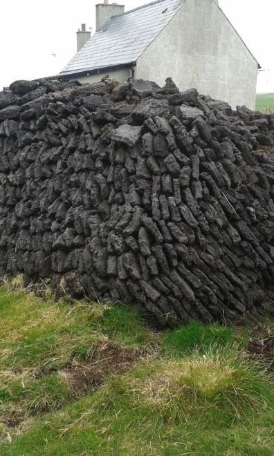 Stack on raised ground with drainage channel.